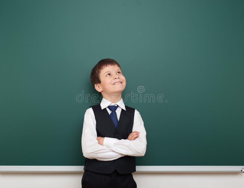 学校学生男孩注视着干净的黑板,做鬼脸和情感,穿戴在一套黑衣服,教育概念,演播室pho 库存图片