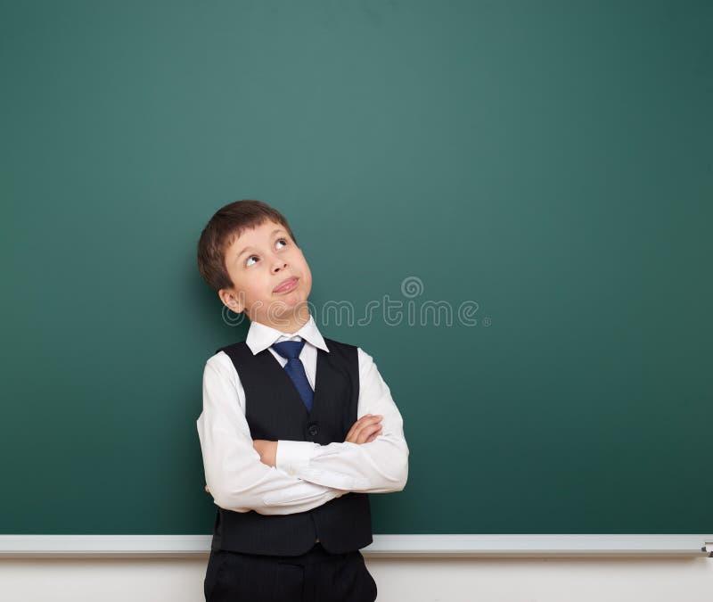 学校学生男孩注视着干净的黑板,做鬼脸和情感,穿戴在一套黑衣服,教育概念,演播室pho 库存照片