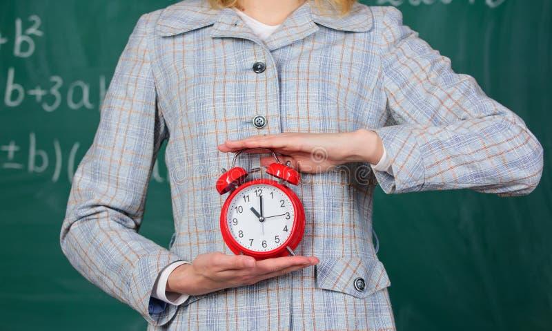 学校学科概念 日程表和政权 闹钟在女性手上关闭  老师属性 闹钟 免版税库存照片