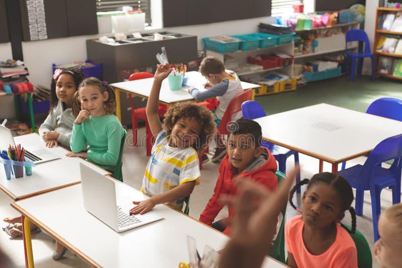 学校孩子行正面图听他们老师和他们中的一个举他的手指answe的 图库摄影