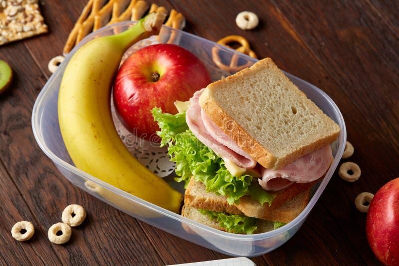 学校或野餐午餐盒用三明治和各种各样的五颜六色的蔬菜和水果在木背景,关闭 图库摄影