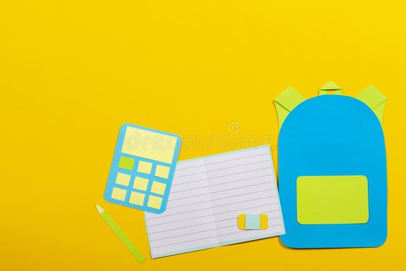 学校教育papercut背景 书包背包、笔记本和计算器纸在黄色背景切开了 免版税库存图片