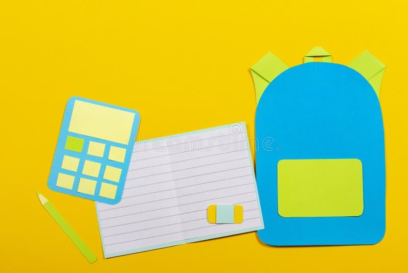 学校教育papercut背景 书包背包、笔记本和计算器纸在黄色背景切开了 库存照片