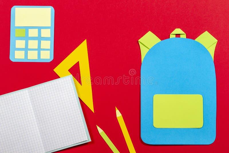 学校教育papercut背景 书包背包,书笔记本学校用品纸在红色背景切开了 免版税库存照片