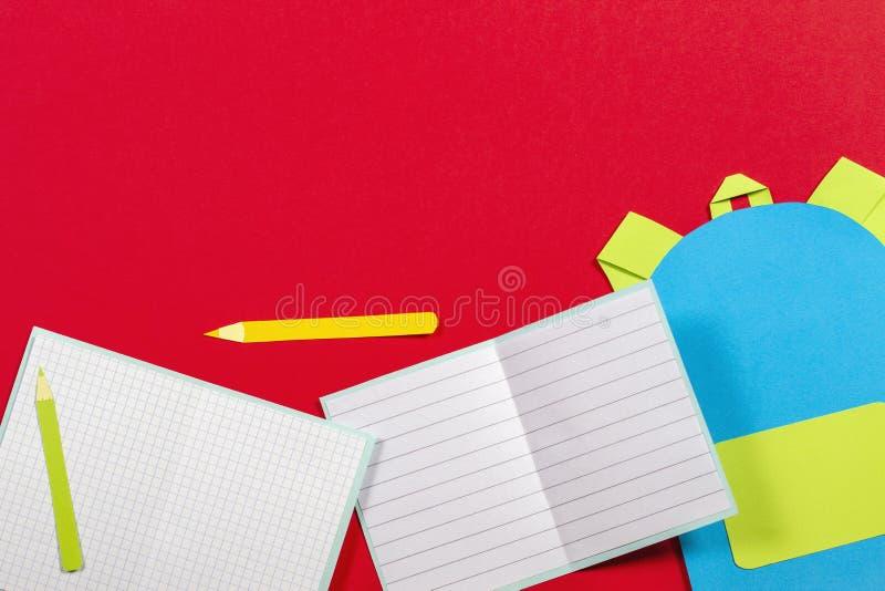 学校教育papercut背景 书包背包,书笔记本学校用品纸在红色背景切开了 免版税库存图片