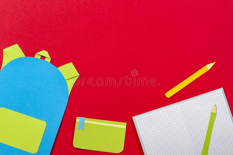 学校教育papercut背景 书包背包,书笔记本学校用品纸在红色背景切开了 库存照片