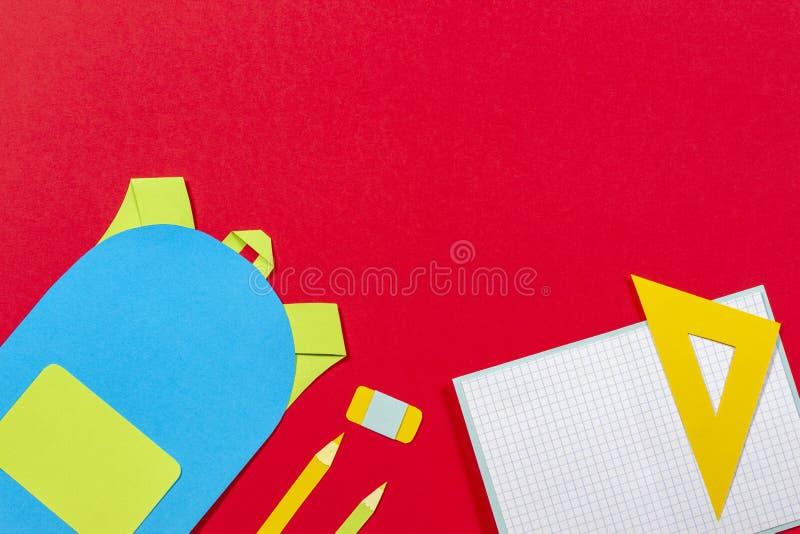 学校教育papercut背景 书包背包,书笔记本学校用品纸在红色背景切开了 库存图片