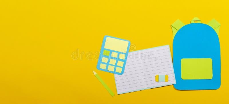 学校教育papercut背景 书包背包,笔记本铅笔计算器纸在黄色背景切开了 免版税库存照片