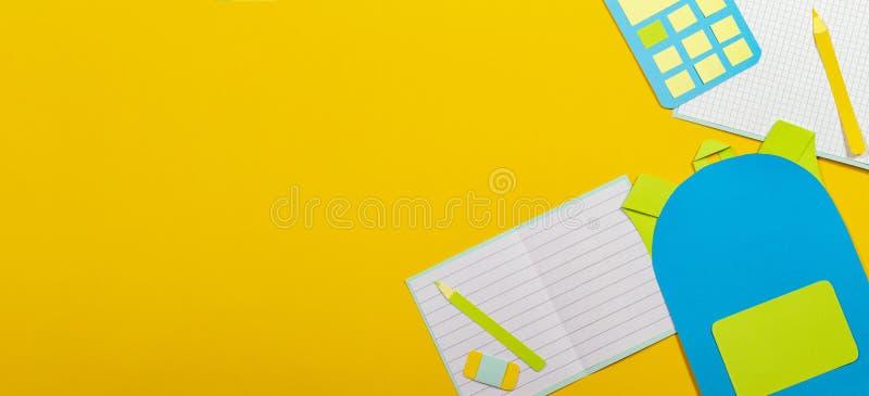 学校教育papercut背景 书包背包,笔记本铅笔计算器纸在黄色背景切开了 库存图片