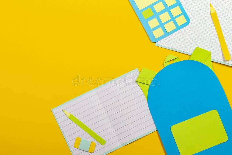 学校教育papercut背景 书包背包,笔记本铅笔计算器纸在黄色背景切开了 免版税图库摄影
