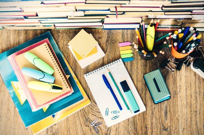 学校文具辅助部件-笔记本,与塑料持有人铅笔,笔,标志,纸夹,贴纸的习字簿堆, 免版税库存图片