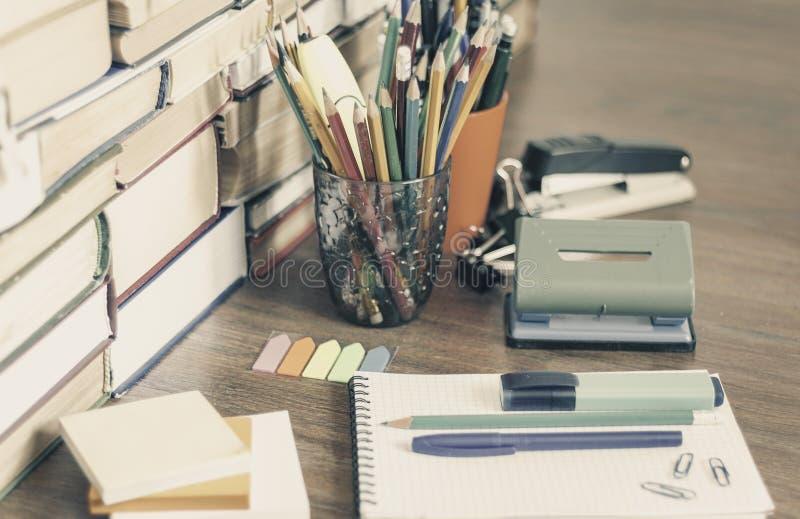 学校文具辅助部件-笔记本,与塑料持有人铅笔,笔,标志,纸夹,贴纸的习字簿堆, 免版税图库摄影