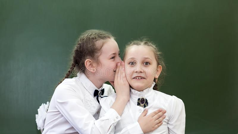 学校朋友告诉在他的耳朵的一个秘密 免版税图库摄影