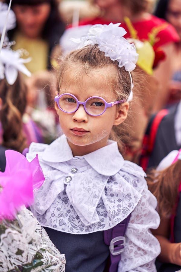 学校欢乐制服的一个女孩孩子有弓、玻璃和一个书包的在她在孩子人群站立并且回来  免版税库存图片