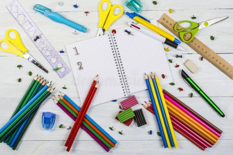 学校用品和一句开放笔记本谎言在白色木背景 图库摄影