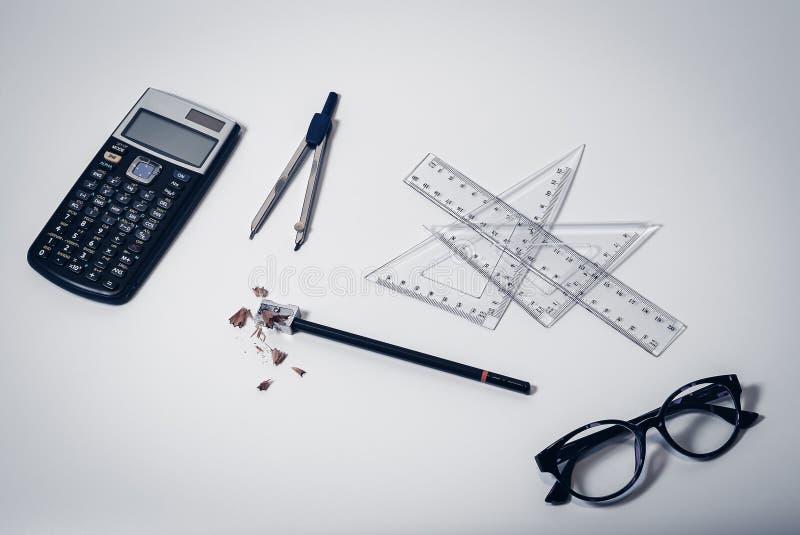学校用品顶视图在干净的白色桌面背景的与计算器、纸指南针、统治者、玻璃和铅笔 免版税库存图片