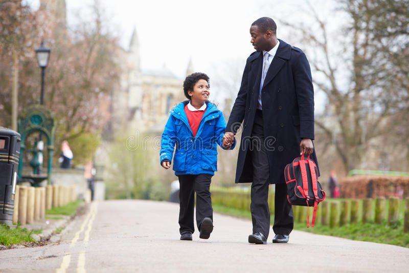 学校的父亲走的儿子沿道路 图库摄影