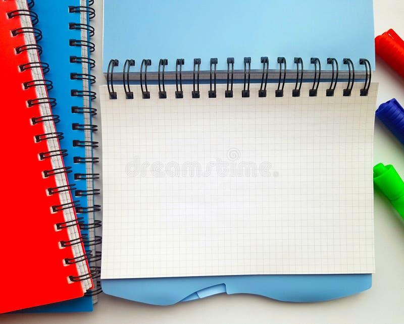 学校的空白的笔记本有记号笔的 在白色背景隔绝的堆五颜六色的笔记本 蓝色,红色,绿色,白色 图库摄影