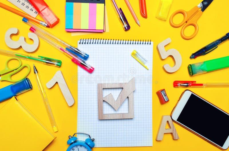 学校竞选概念 竞选在一张书桌上的复选框和学校辅助部件在黄色背景 教育 文具,手表 图库摄影