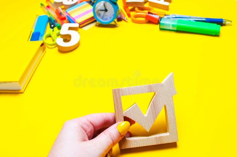 学校竞选概念 竞选在一张书桌上的复选框和学校辅助部件在黄色背景 教育 文具,手表 免版税库存照片