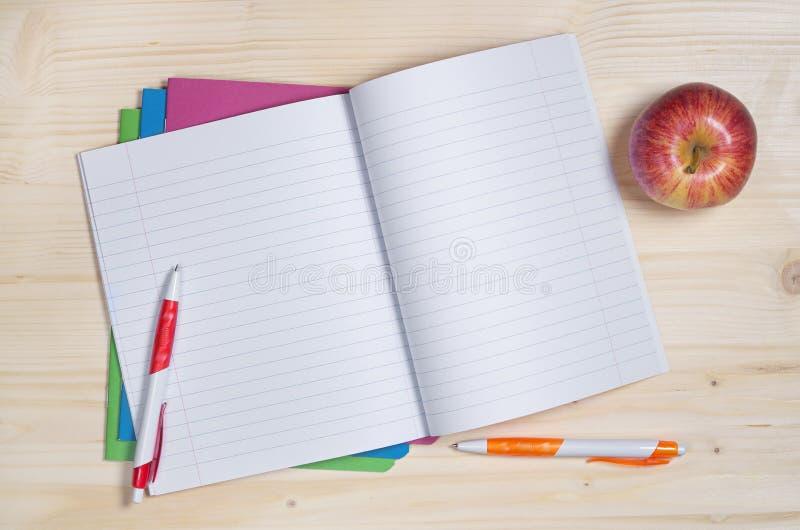学校笔记本、笔和苹果 图库摄影