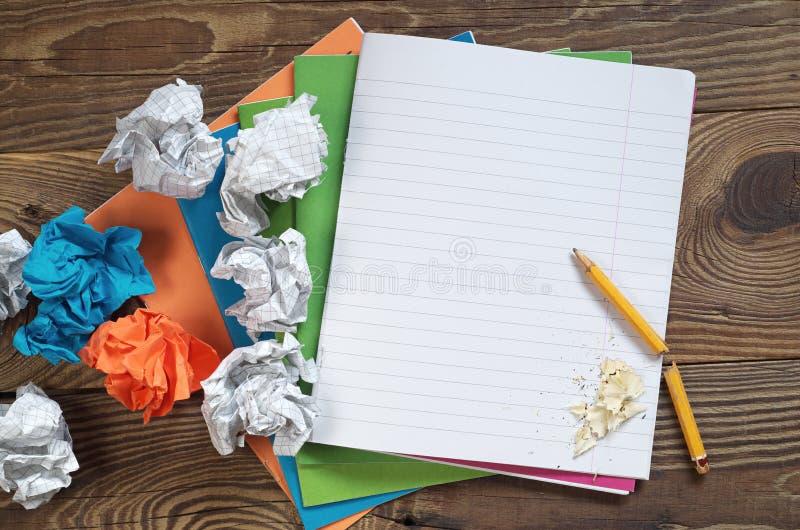 学校笔记本和被弄皱的纸球 免版税图库摄影