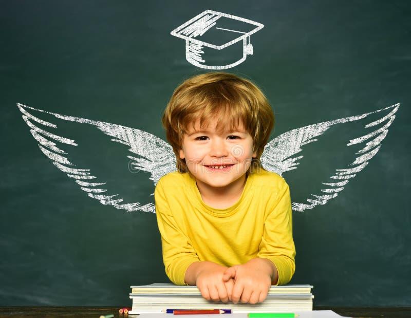 学校翼和梦想 愉快的学校孩子 E ?? 指向在黑板的滑稽的小男孩 ?? 免版税库存图片