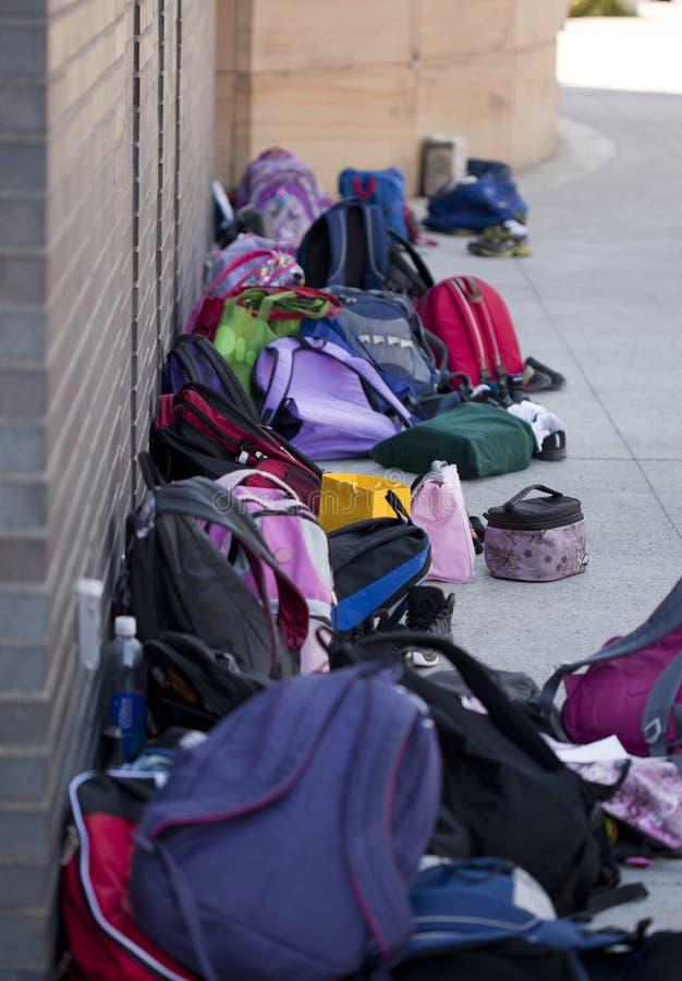 学校背包对墙壁 免版税库存照片