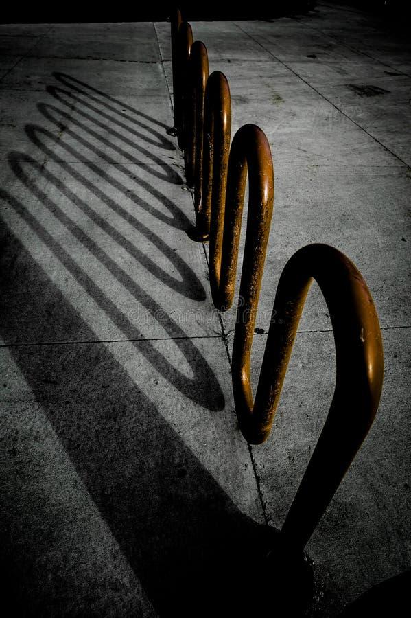 学校自行车架上的阴影 免版税库存图片