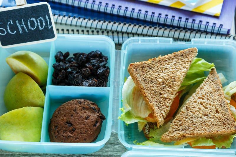 学校蓝色饭盒用自创三明治,绿色苹果,曲奇饼,铅笔,时钟,在桌上的笔记本 库存图片