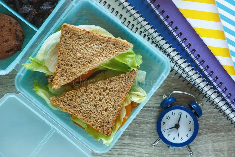学校蓝色饭盒用自创三明治,绿色苹果,曲奇饼,铅笔,时钟,在桌上的笔记本 免版税图库摄影