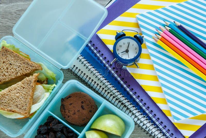 学校蓝色饭盒用自创三明治,绿色苹果,曲奇饼,铅笔,时钟,在桌上的笔记本 免版税库存照片