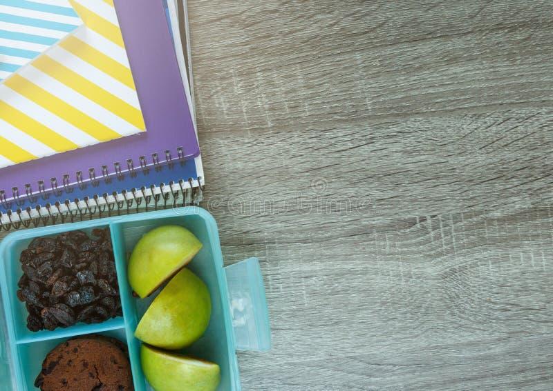 学校蓝色饭盒用自创三明治,绿色苹果,曲奇饼,铅笔,时钟,在桌上的笔记本 E 库存照片