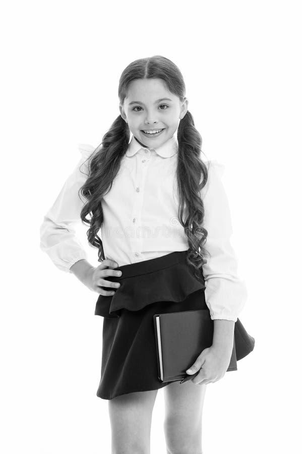 学校课本和文具概念 儿童校服聪明的孩子愉快的举行课本 女孩愉快的面孔运载 库存图片
