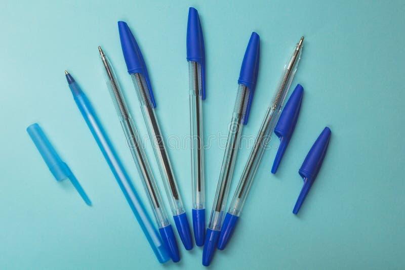 学校辅助部件,在蓝色背景的蓝色笔 库存照片