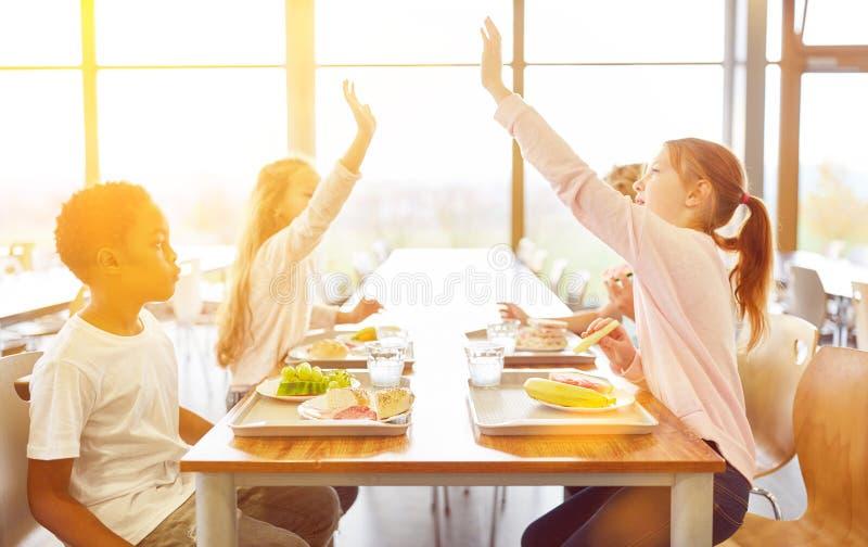 学校食堂的孩子做高五 库存照片
