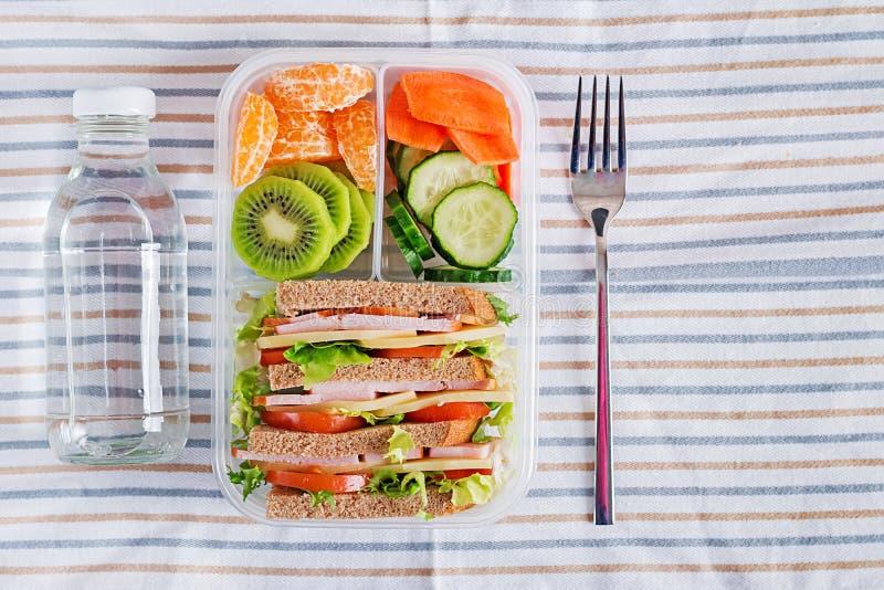 学校饭盒用三明治、蔬菜、水和水果在桌上 库存图片