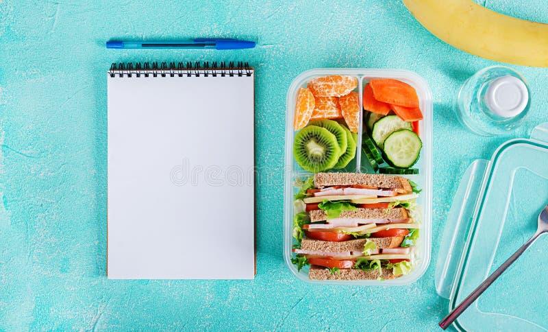 学校饭盒用三明治、蔬菜、水和水果在桌上 免版税库存图片