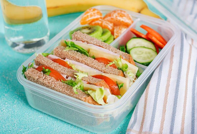 学校饭盒用三明治、蔬菜、水和水果在桌上 免版税库存照片