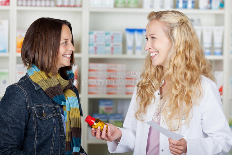 给医学瓶的药剂师女性顾客 免版税库存照片