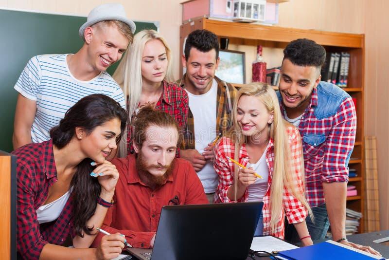 学生与Using教授坐在书桌的便携式计算机的高中小组,青年人老师谈论 免版税图库摄影