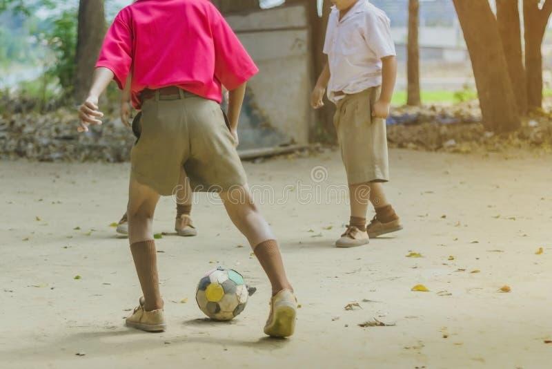 学生享用踢与他的朋友的老橄榄球在地面上 免版税库存图片