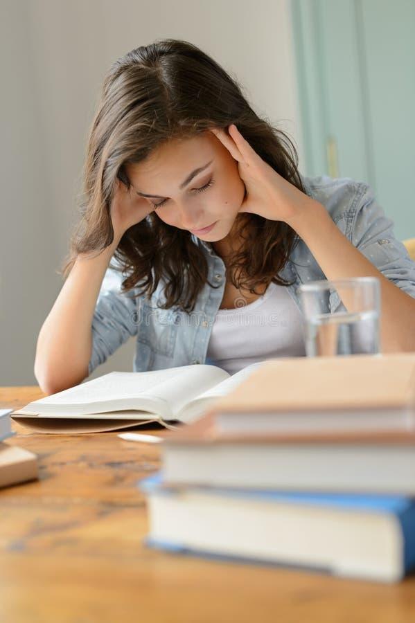 学生十几岁的女孩集中阅读书家 库存图片