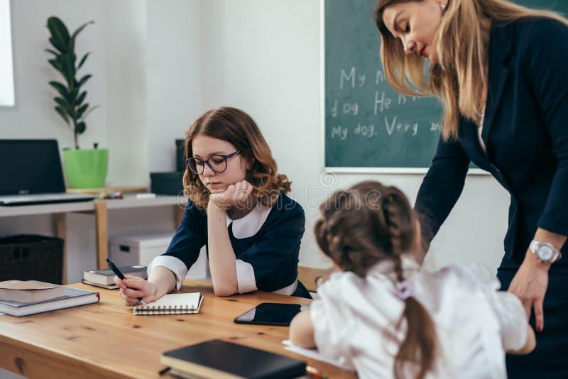 学生和女性白种人老师在教室 库存照片