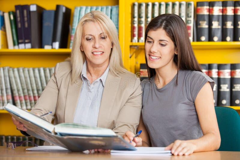 学生和老师一起阅读书在表上 免版税库存照片