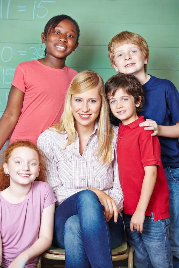 学生和老师在黑板前面 免版税图库摄影