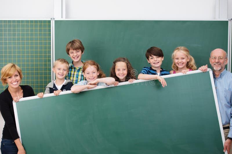 年轻学生和老师愉快的学校队  免版税库存图片