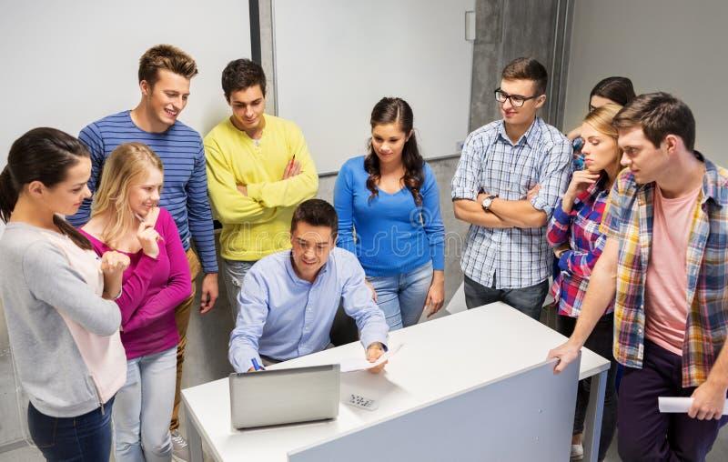 学生和老师有纸和膝上型计算机的 免版税库存照片