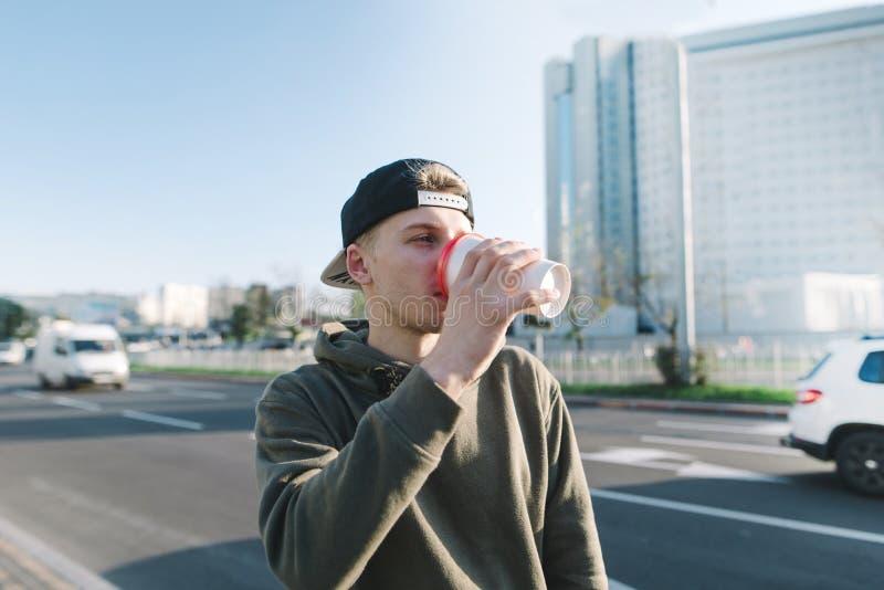 学生在城市附近喝步行的一份热的饮料 年轻人在街道背景站立并且喝咖啡 的生活方式 免版税图库摄影