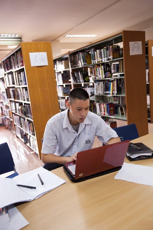 学生在大学图书馆里做他的家庭作业 库存照片